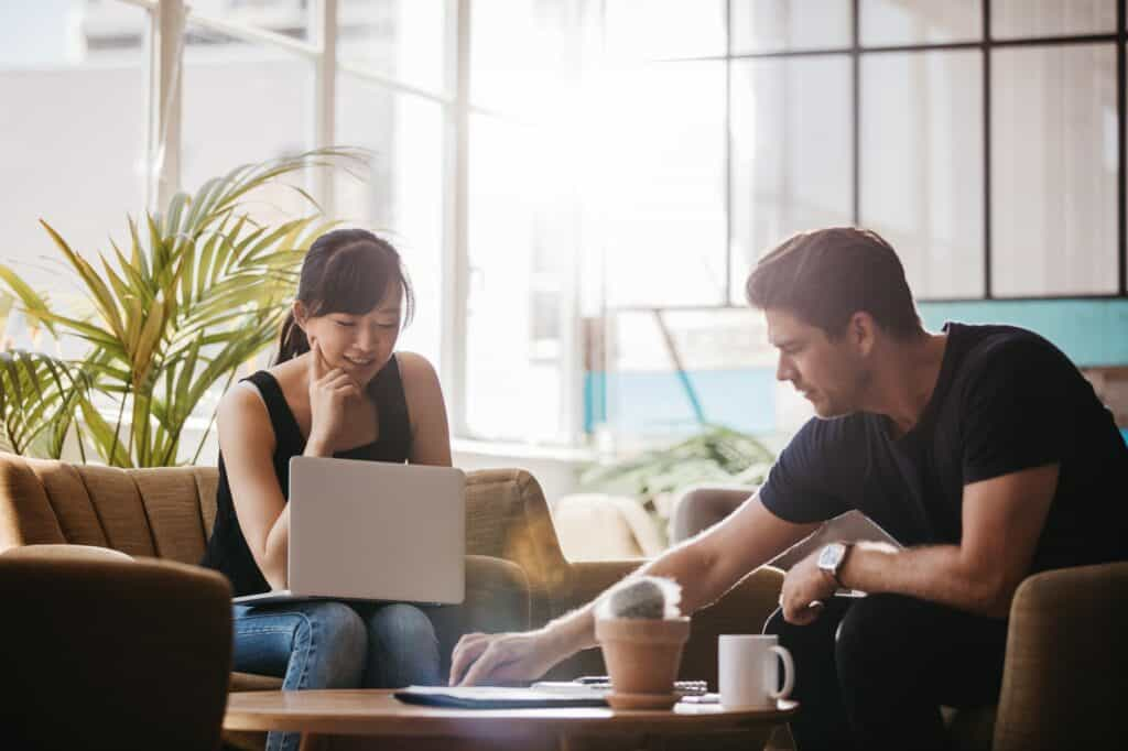 Two people working together in office lobby
